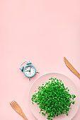 Alarm clock, cutlery and plate with greenery on pink. Intermittent fasting, lunchtime and dieting concept.