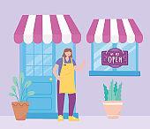 we are open sign, front view store door window employee and plants