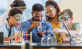 Multi-ethnic teacher and students in chemistry lab