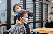 Young man getting haircut by hairdresser, Barber using scissors and comb, New normal concept