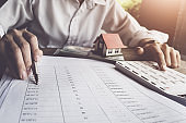Customers use pens and calculators to calculate home purchase loans according to loan documents received from the bank. real estate concept.