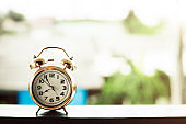 Bell alarm clock against blurred outdoor background with copy space for time management concept
