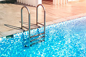 metal staircase leads to the pool. Blue water in the pool of a large house, hotel