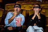 Man and woman in the cinema watching a 3D movie