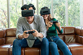 Young happy Asian couple playing video gamesYoung happy Asian couple playing video games