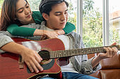 Young Asian Couple Plays Guitar and Sing Song