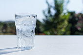 a glass of water with ice on the table.