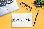 New normal concept effected by COVID 19 coronavirus that changes our lifestyle to new normal presented in word written in notebook on office desk when abnormal becomes new normal .