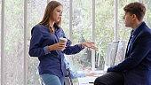 Businesswoman and businessman having conversation.