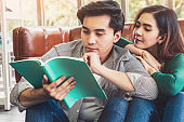 Young Asian couple reading book in living room.