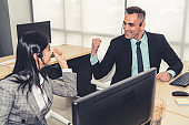 Business people wearing headset celebrate working in office