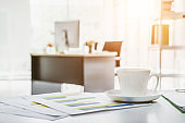 Coffee cup on office table with background of modern office.