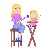 Mother Feeds Daughter Holds Spoon on Highchair