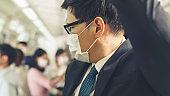 Young man wearing face mask travels on crowded subway train