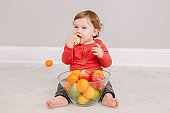 Cute adorable Caucasian baby boy eating citrus fruit. Finny child eating healthy organic snack. Solid finger supplementary food for children toddlers.