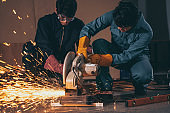 Professional mechanic man is cutting steel metal with rotating carbon blade