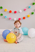 Funny Caucasian baby boy celebrating first birthday. Child kid toddler sitting on floor with colorful balloons. Celebration of event or party indoors at home. Happy birthday lifestyle concept.