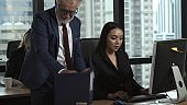 Senior manager gives advice to young woman worker.