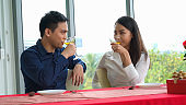 Happy romantic couple eating lunch at restaurant