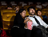 Audience sit in a cinema and watch horror movie
