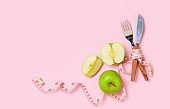 Green apple with measuring tape around fork and knife isolated on pink background,