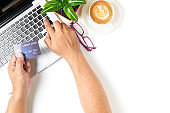 man using credit card for online shopping on white table with latte art hot coffee isolated