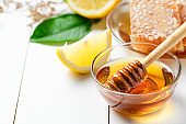 Honey with wooden honey dipper in bowl with sliced lemon