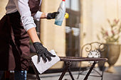 Female in gloves preparing cafe for open the guest