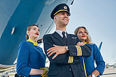 Dreamy stewardesses standing behind the pilot with folded arms
