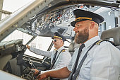 Contented experienced men navigating the aircraft and smiling