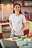 Laughing housewife getting distracted from cutting salad components