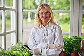 Cheerful biologist wearing a lab coat and gloves
