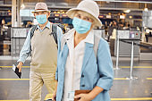 Passengers in face masks standing at the airport