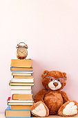 Stuffed toy Teddy bear with glasses, a stack of books and alarm clock. Education concept, back to school.