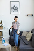 Maid using vacuum cleaner at home