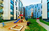 Modern residential apartment flat house building and children playground reflex