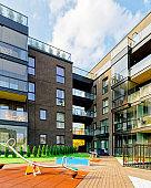 Children playground and Modern architecture of apartment building reflex