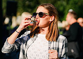 Young smiling girl wearing sunglasses drinking water from glass