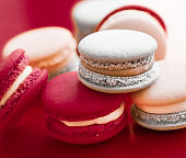 French macaroons on wine red background, parisian chic cafe dessert, sweet food and cake macaron for luxury confectionery brand, holiday backdrop design