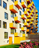 Apartment residential modern house building exterior with flowers and fence reflex