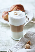 Glass of Latte Macchiato with Croissant. Bright wooden background. Close up.