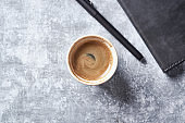 Cup of coffee on rustic wooden background. Top view. Copy space.