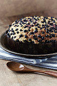Simple Cake with Bilberries on wooden background.