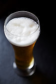 Glass of beer on dark background. Close up.