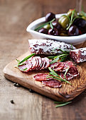 Sliced french salami with fresh rosemary on rustic wooden background.