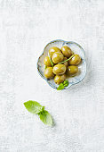 Green olives on bright wooden background. Top view. Copy space.