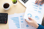Businessman is inspecting and checking the business reports graphs to audit the financial reports. Analyzing the revenue and auditing the budget concept.