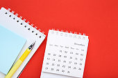 Calendar page with notepad and pen on red background