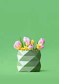 Minimalist festive concept, front view of green vase with spring season flowers bouquet