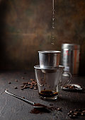 Preparation of Vietnamese coffe with aluminum cofe filer on dark background